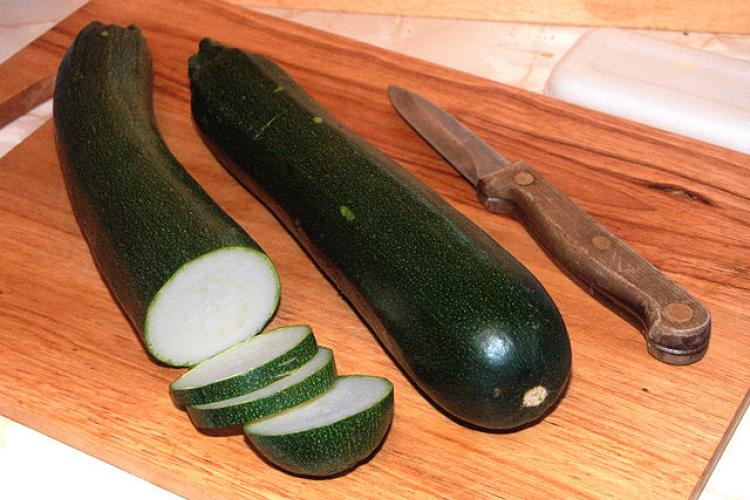 Two zucchini on a table, one of them half cut into slices.