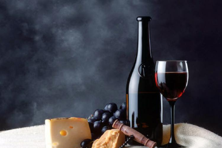 A bottle and a glass of red wine, cheese and grapes on a table.