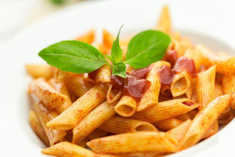 Penne pasta with tomato sauce and chorizo in a bowl decorated with basil leaves.