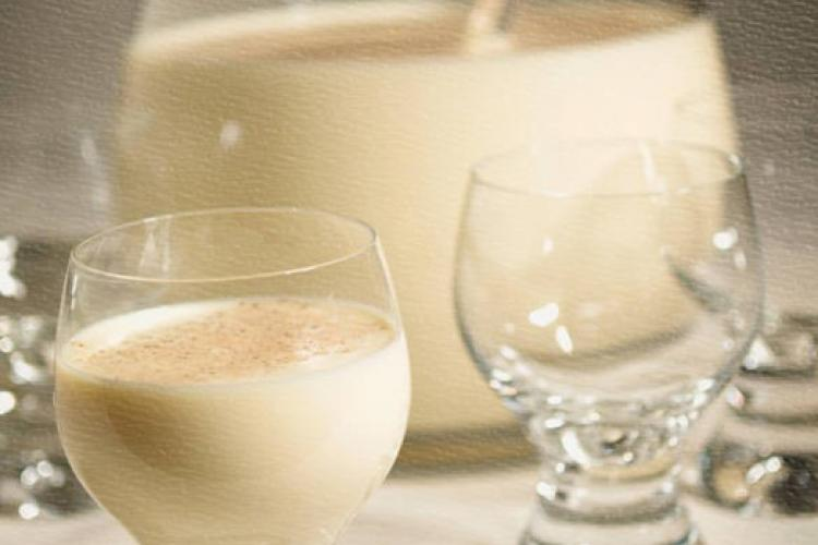 Eggnog in a punch bowl with serving spoon and glasses.