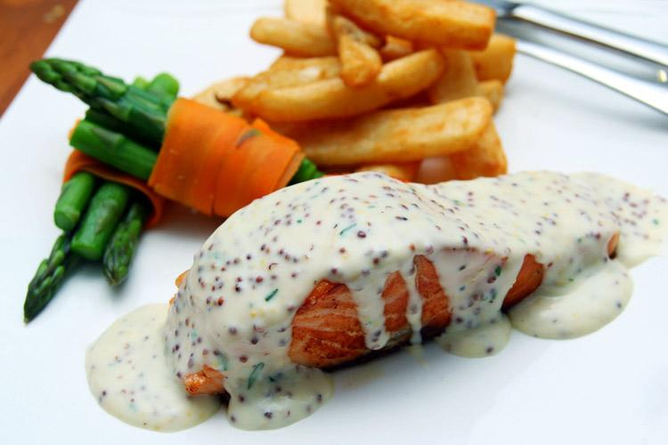 Salmon with mustard sauce, asparagus and French fries on a plate.