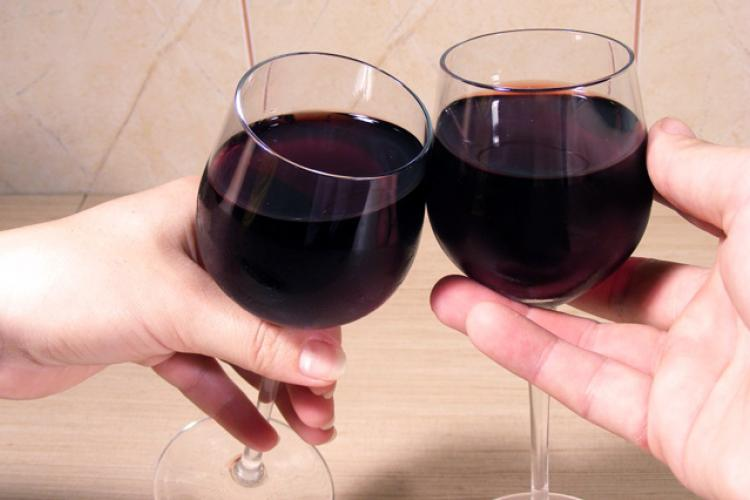 Two hands clicking glasses of red wine.