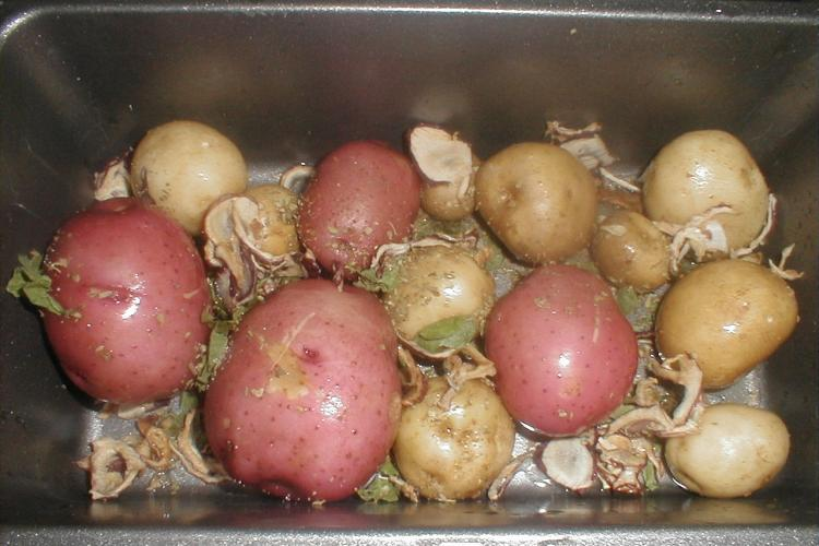 Red and white potatoes roasting in a roast pan.