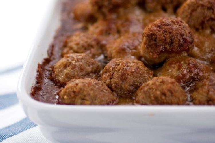 Meatballs in tomato sauce baked in a white oven tray.