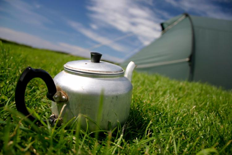A metal kettle sitting on the green in front of a camping tent.