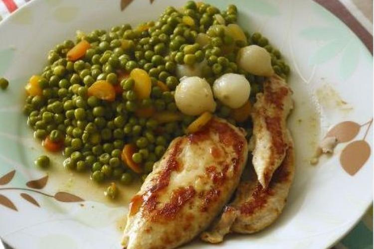 Grilled chicken breast with French style peas.