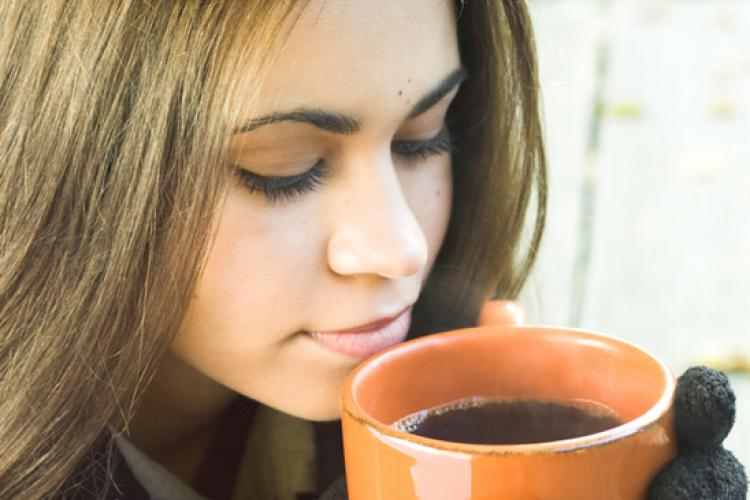 Young woman with a cup of coffe in her hands.