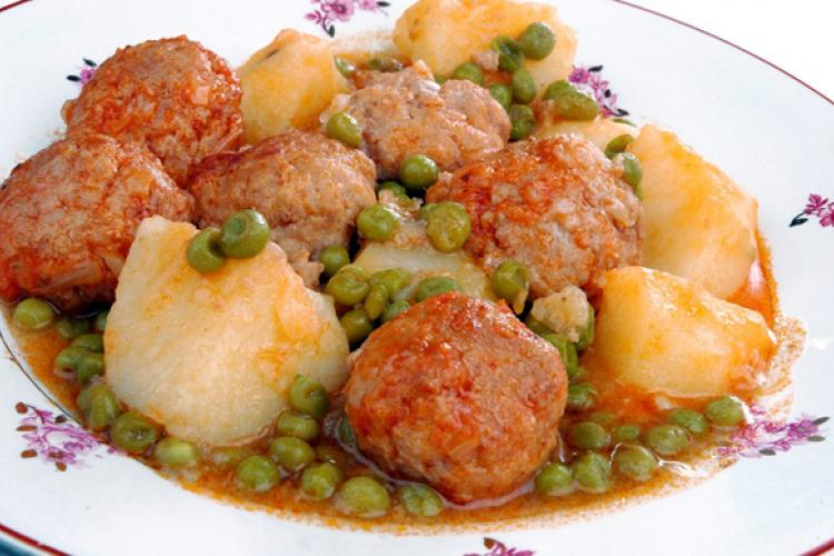 Meatballs in sauce with peas and potatoes.