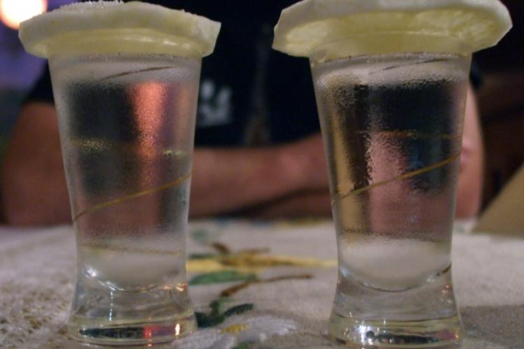 Two glasses with vodka covered by slices of lemon.