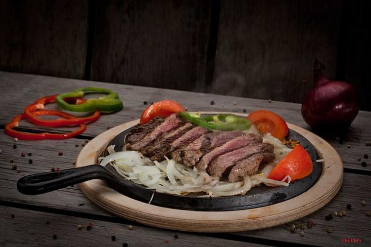 Beef fajitas with pepper, onion and tomato.