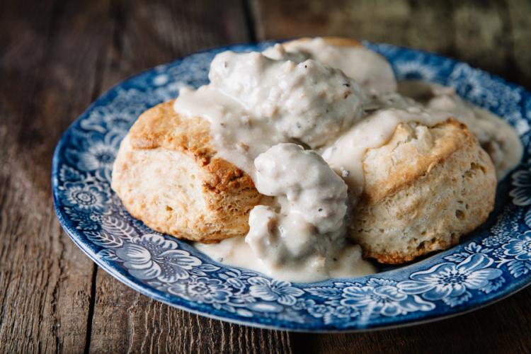 Southern biscuits and gravy on a china plate.