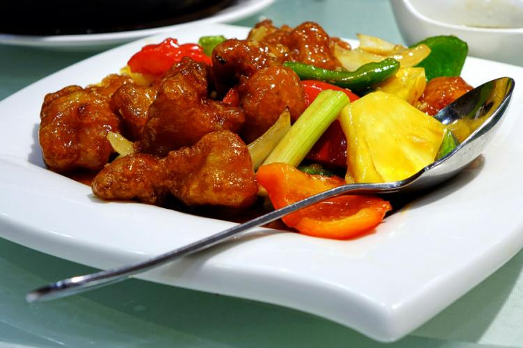 Sweet and sour pork in a whte serving plate.