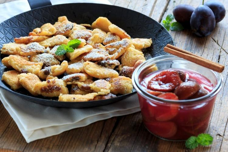 Kaiserschmarrn with plum compote in a pan.