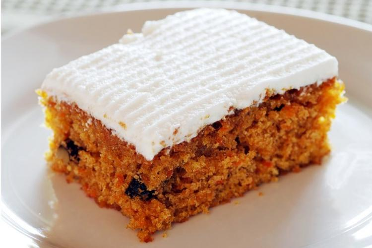 A piece of banana and carrot cake with icing.