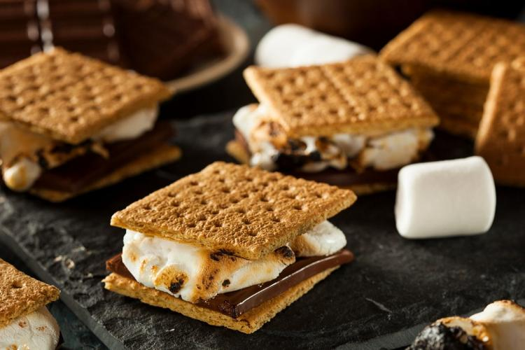 S´mores on a counter top, made with graham crackers, white marshmallows and thick chocolate.