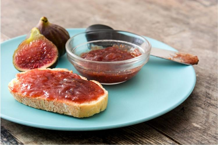 Sweet fig preserve on toast on a table with more fig jam and figs.