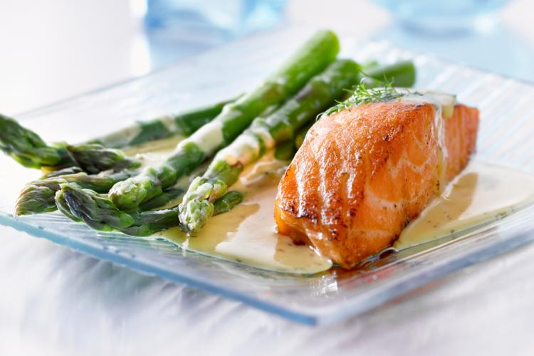 Baked salmon with sauce and asparagus.