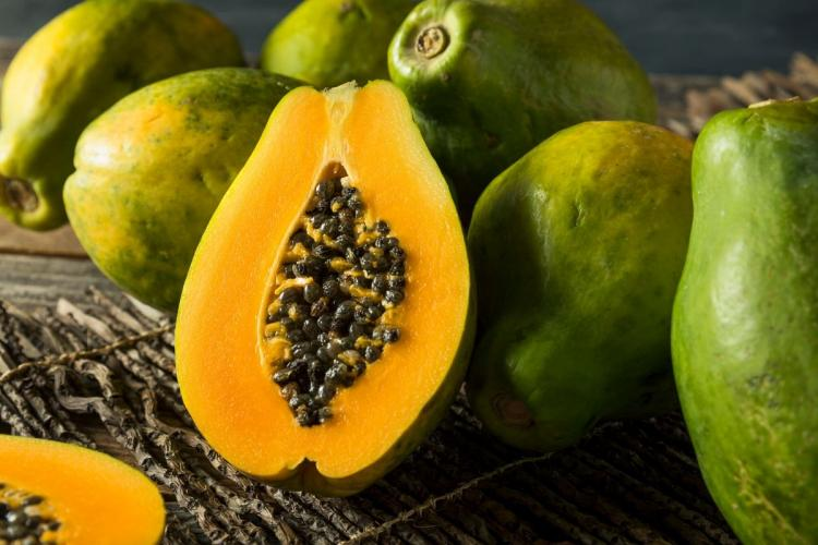 Papaya cut in half and whole papayas.