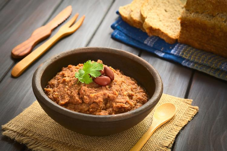Home made red kidney bean dip garnished with red kidney beans and coriander in a rustic bowl.