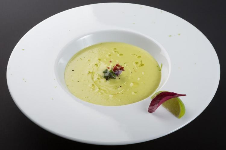 Chilled avocado soup in a plate decorated with lettuce and lime.