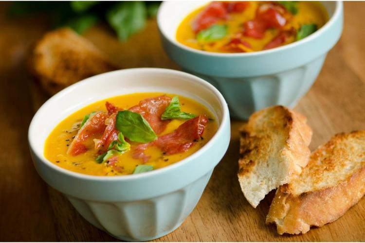 Melon and serrano ham soup, decorated with basil and served with toasted bread.
