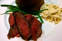 Grilled sirloin, cooked rare, with green beans, gravy, and horseradish on a plate.