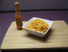 Yellow colored Mexican rice in a square bowl.