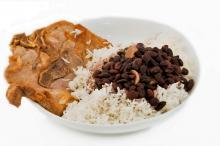 A plate with pork, rice and black bean soup from Cuba.