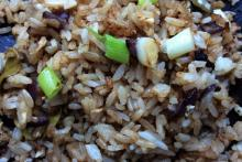 Detail of Thai fried rice with red onion, spring onios and egg.