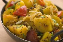 Bombay potatoes in an typical Indian serving pan.