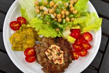 Savory lamb burger with cheese cream, picalilli, lettuce and chickpea salad.